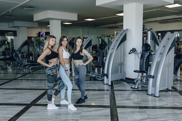 Attraktive mädchen in sportbekleidung im fitnessstudio kommunizieren. sportleben und fitnessatmosphäre.