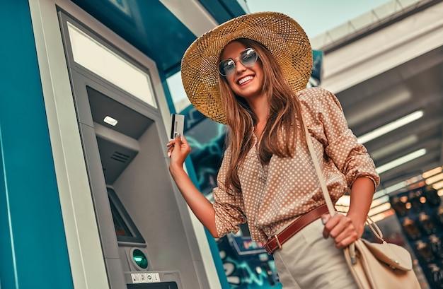 Attraktive mädchen touristin in sonnenbrille, bluse und strohhut verwendet eine kreditkarte in der nähe des geldautomaten. das konzept von tourismus, reisen, freizeit.