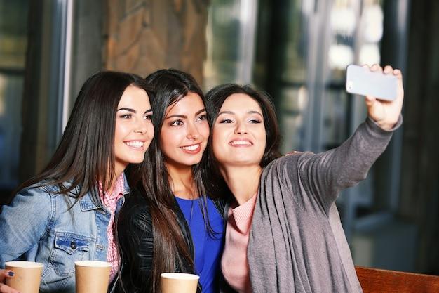 Attraktive mädchen zusammen nehmen selfie, das im café sitzt