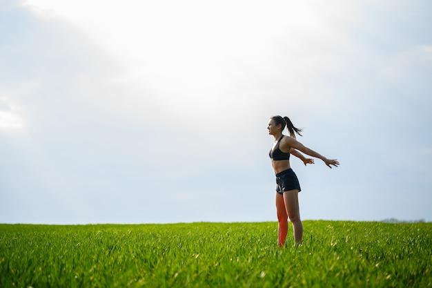 Attraktive mädchenathletin macht aufwärmen im freien, übungen für die muskeln. junge frau macht sport, gesunden lebensstil, athletischen körper. sie trägt sportkleidung, schwarzes top und shorts