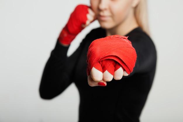 Attraktive mma-sportlerin in der hand wickeln die aufstellung ein. isoliert auf weißem hintergrund