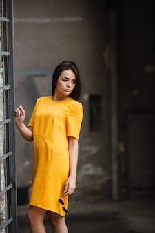Attraktive modefrau im orangefarbenen kleid posiert in der nähe der weißen wand