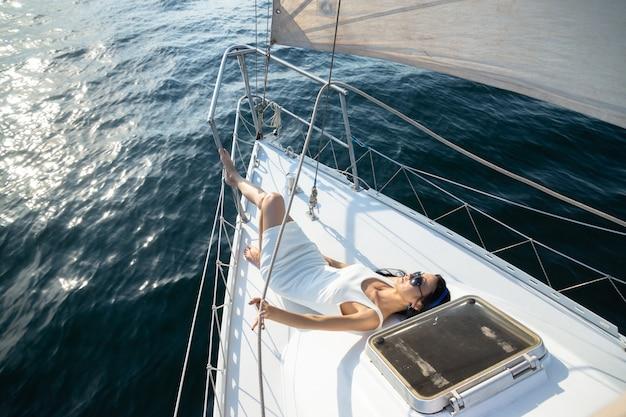 Attraktive modefrau in einem weißen kleid liegt auf der plattform einer yacht.