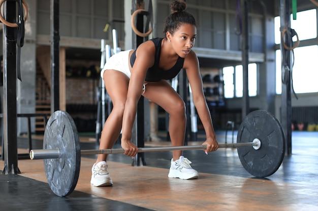 Attraktive muskulöse sitzfrau, die gebäudemuskeln trainiert.