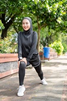 Attraktive muslimische asiatische frau strekth ihr bein während der sportzeit im freien an sonnigem tag
