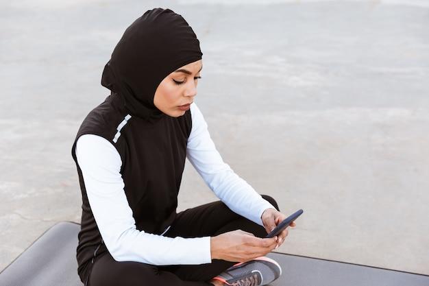 Attraktive muslimische sportlerin, die im freien hijab trägt, auf einer fitnessmatte sitzt und handy benutzt