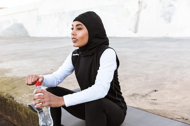 Attraktive muslimische sportlerin, die im freien hijab trägt, auf einer fitnessmatte sitzt und wasser trinkt