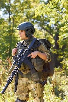 Attraktive mutige militärfrau mit einer waffe im wald