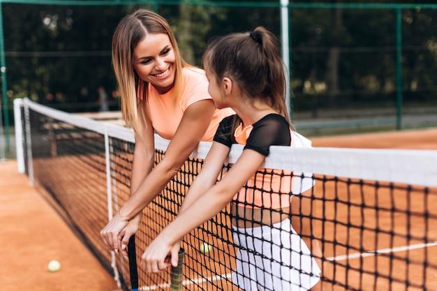 Attraktive mutter und tochter auf dem tennisplatz, der das sprechen über das spielen von tennis bewundert