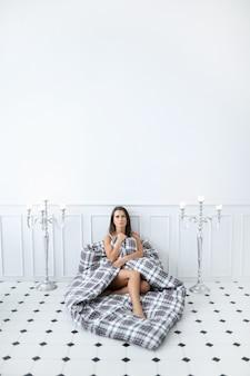 Attraktive nackte frau im bett, die sich mit bettdecke bedeckt