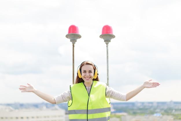 Attraktive nette arbeitskraftfrau im grünen westen und ohrenschützer stehen auf dach, halten tablette