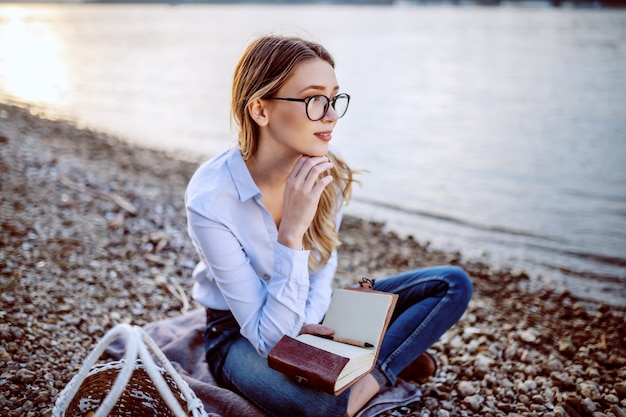 Attraktive niedliche kaukasische modische junge frau mit brillen, die an der küste nahe fluss sitzen, denken und notizbuch halten.