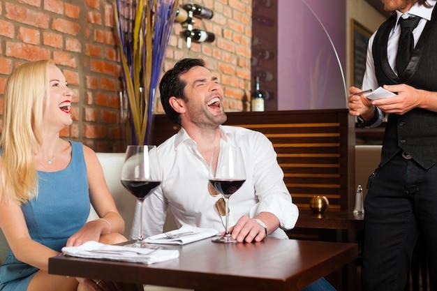 Attraktive paare, die rotwein im restaurant oder in der bar trinken