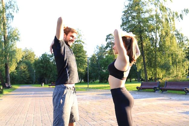 Attraktive paare, die sich zusammen strecken und lächeln, während sie im park draußen trainieren.