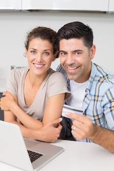 Attraktive Paare, die zusammen Laptop verwenden, um online zu kaufen