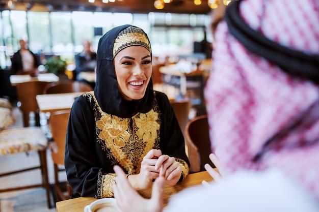 Attraktive positiv lächelnde arabische frau, die mit ihrem geliebten ehemann im café sitzt und plaudert.