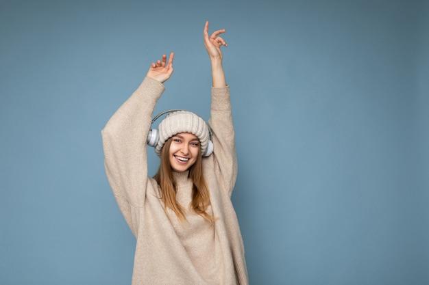 Attraktive positiv lächelnde junge blonde frau, die beige winterpullover und hut lokalisiert trägt