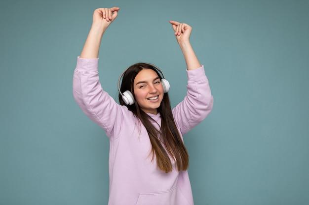 Attraktive positiv lächelnde junge brünette frau mit hellviolettem hoodie isoliert über blau