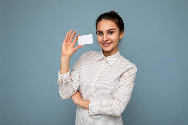 Attraktive positiv lächelnde junge brünette frau mit weißer bluse auf blauem hintergrund isoliert