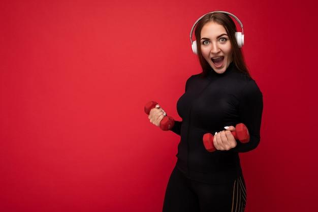 Attraktive positiv lächelnde junge brünette frau trägt schwarze sportkleidung isoliert auf rot