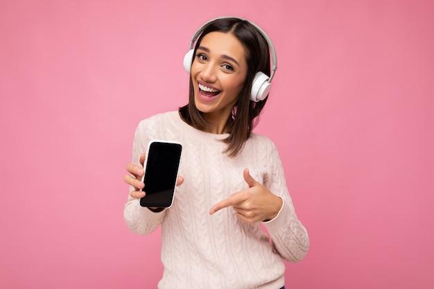 Attraktive positiv lächelnde junge frau, die ein stilvolles, lässiges outfit trägt, isoliert auf einer bunten hintergrundwand, die ein mobiltelefon mit leerem bildschirm für den ausschnitt mit weißem bluetooth-kopfhörer hält und zeigt