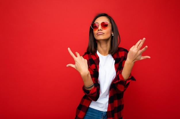 Attraktive positive amüsante lustige junge brünette frau im lässigen weißen t-shirt für mockup, stilvolles rotes karohemd und trendige rote sonnenbrille einzeln auf rotem hintergrund mit kopienraum.