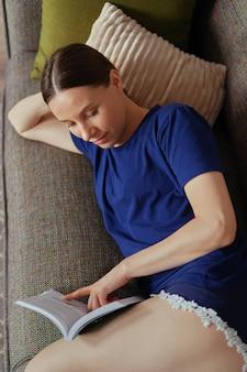 Attraktive positive frau, die ein buch liest, das sich auf dem sofa entspannt