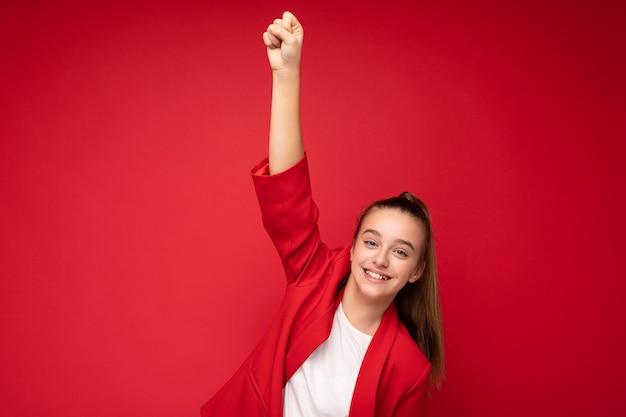 Attraktive positive glücklich lächelnde brünette kleine teenagerin mit trendiger roter jacke und weißem t-shirt, die isoliert über roter hintergrundwand steht und in die kamera schaut und den sieg feiert. kopieren