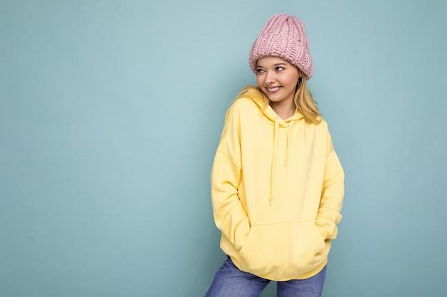Attraktive positive glückliche junge blonde frau lokalisiert über bunter hintergrundwand, die lässig trägt