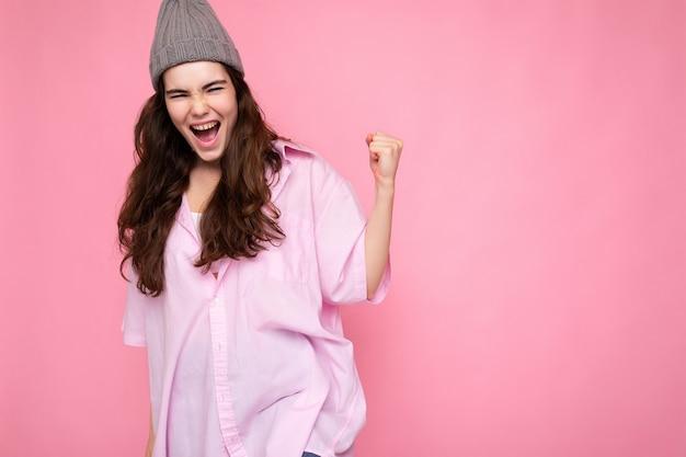 Attraktive positive glückliche junge lockige brünette frau mit rosa hemd und grauem hut isoliert auf