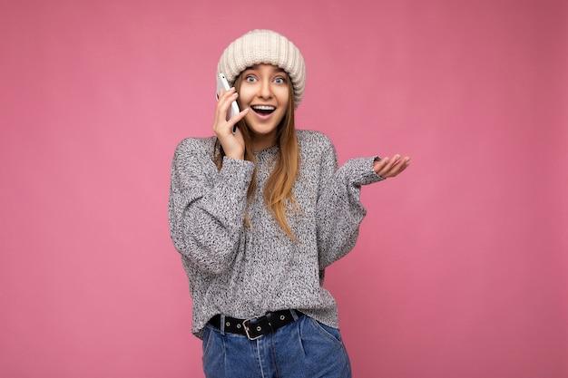 Attraktive positive glückliche überraschte junge blonde frau, die lässigen grauen pullover und beige hut lokalisiert über rosa hält in der hand trägt und auf handy kommuniziert, das kamera betrachtet.