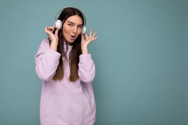 Attraktive positive junge brünette frau mit hellviolettem hoodie auf blauem hintergrund isoliert