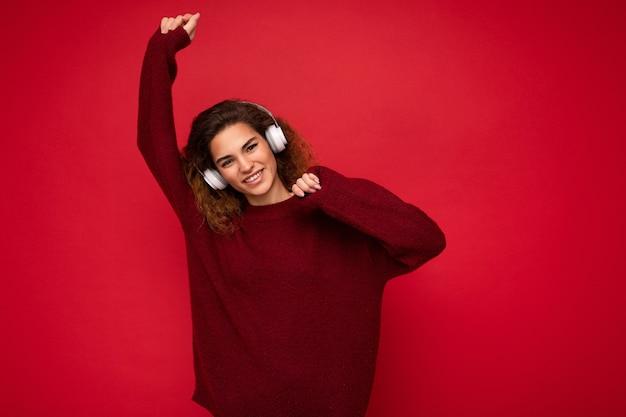 Attraktive positive junge brünette lockige frau mit dunkelrotem pullover auf rotem hintergrund isoliert