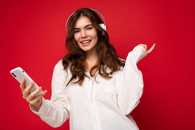 Attraktive positive junge brünette lockige frau mit weißem hemd isoliert auf roter hintergrundwand
