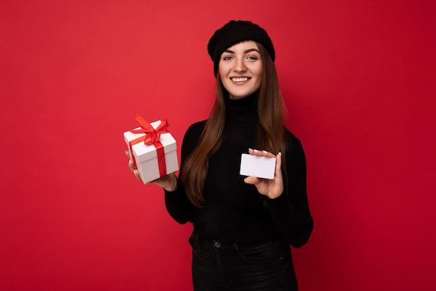 Attraktive positive junge brünette weibliche person mit schwarzem pullover und hut isoliert auf rotem hintergrund mit kreditkarte und geschenkbox mit blick auf die kamera