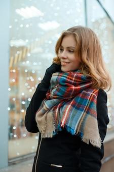 Attraktive positive junge frau mit einem wunderbaren lächeln in einem schwarzen wintermantel in stilvollen handschuhen mit einem wollmode-schal steht in der nähe des mit festlichen lichtern geschmückten schaufensters. glückliches mädchen