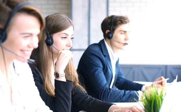 Attraktive positive junge geschäftsleute und kollegen in einem callcenter-büro.