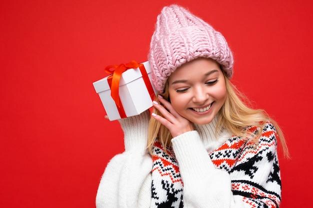 Attraktive positive lächelnde junge blonde frau isoliert über roter hintergrundwand mit winterpullover und rosa hut, die weiße geschenkbox mit rotem band hält und nach unten schaut.