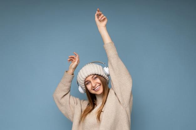Attraktive positive lächelnde junge blonde frau mit beigem winterpullover und hut isoliert über