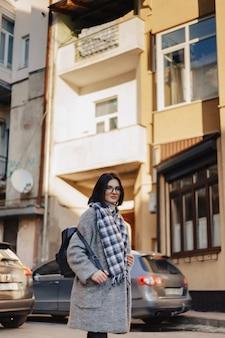 Attraktive positive tragende gläser des jungen mädchens in einem mantel auf dem hintergrund von gebäuden auf autos