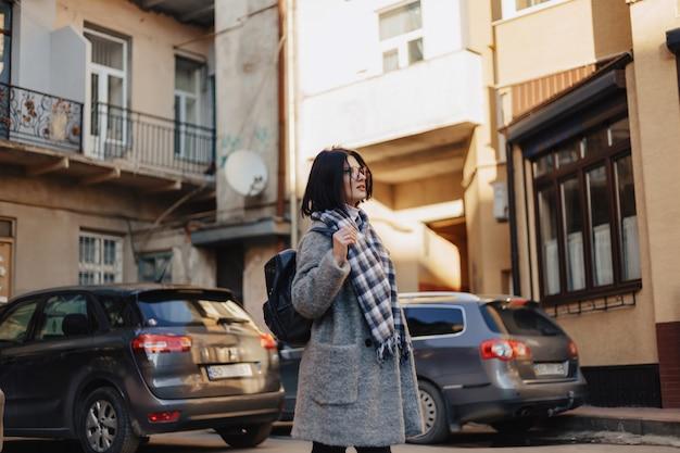 Attraktive positive tragende gläser des jungen mädchens in einem mantel auf der oberfläche von gebäuden auf autos
