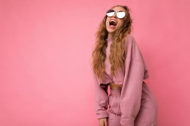 Attraktive positive überglückliche junge blonde frau, die alltägliche stilvolle kleidung und moderne sonnenbrillen trägt, isoliert auf bunter hintergrundwand und spaß hat