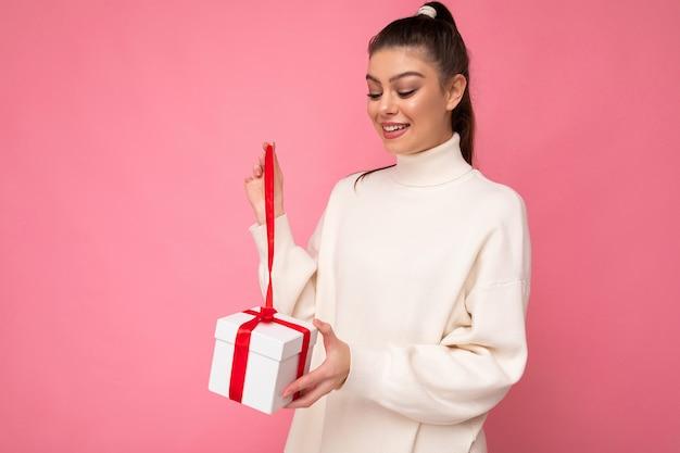 Attraktive positive überraschte junge brünette frau lokalisiert über rosa hintergrundwand, die weißen pullover hält, der geschenkbox hält und geschenk entpackt, das box betrachtet.