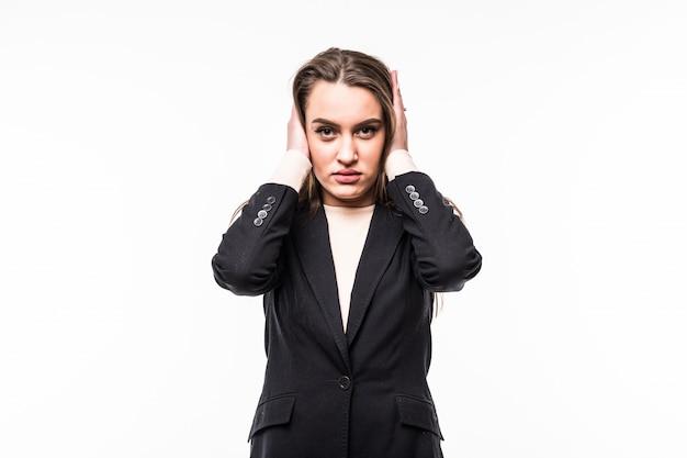 Attraktive professionelle frau, die schwarze kleidersuite trägt, bedeckt ihre ohren mit den händen auf einem weiß.