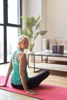 Attraktive reife blonde frau, die beim üben von yoga auf dem boden in die kamera schaut und