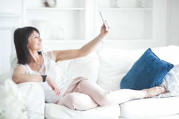 Attraktive reife frau, die auf dem mobiltelefon spricht und selfie macht. erwachsene dame, die zuhause smartphone hält.