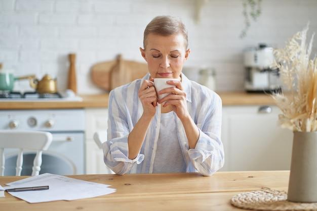 Attraktive reife frau, die den tag mit kaffee beginnt, während sie am holztisch in der küche sitzt