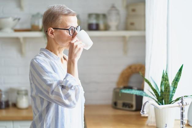 Attraktive reife frau, die den tag mit kaffee beginnt, während sie zum fenster in der küche schaut