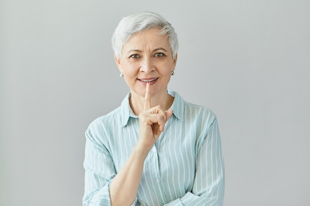 Attraktive reife geschäftsfrau mit pixie-frisur posiert isoliert, hält zeigefinger angehoben, mit vielen tollen ideen. schöne frau mittleren alters, die vorderfinger erhebt, um aufmerksamkeit zu ziehen