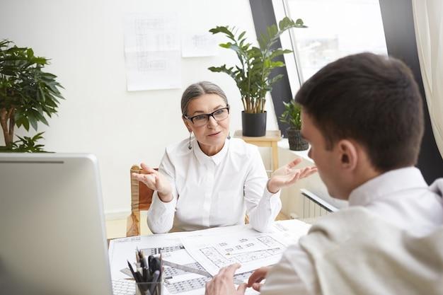 Attraktive reife weibliche geschäftsführerin in brille und weißem hemd, die an ihrem arbeitsplatz sitzt und junge talentierte männliche bewerber für die position des chefarchitekten interviewt und ihn nach berufserfahrung und fähigkeiten fragt